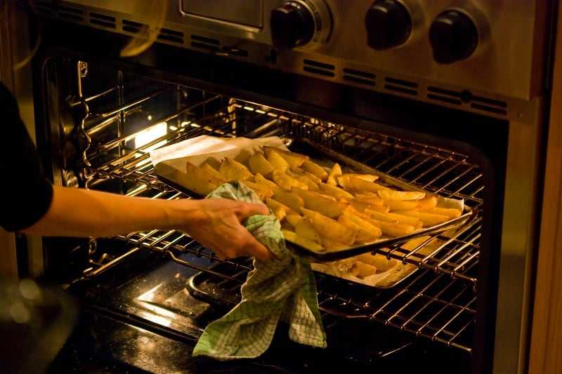 Woman putting tray of potato wedges in oven
