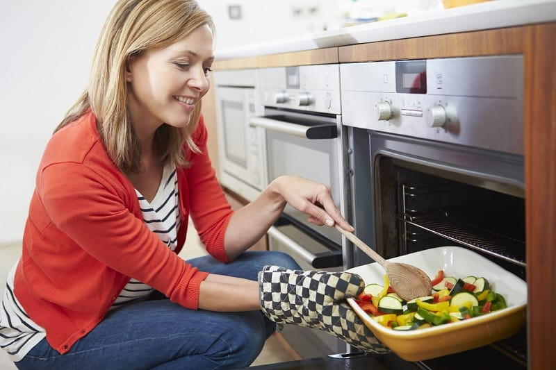 Woman putting tray of vegetables into built-under oven