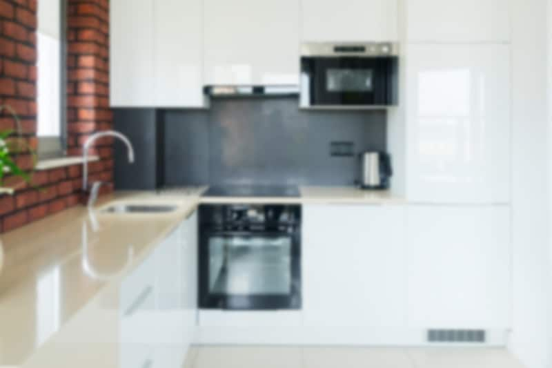 Blurry white kitchen with black cooker