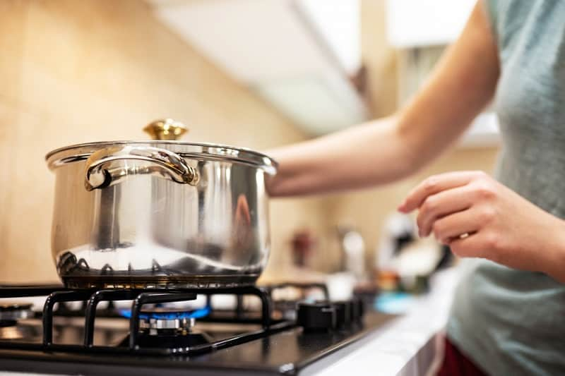 Woman placing steel saucepan on gas hob