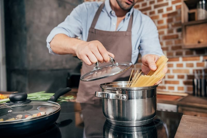 Man Cooking Spaghetti in Saucepan